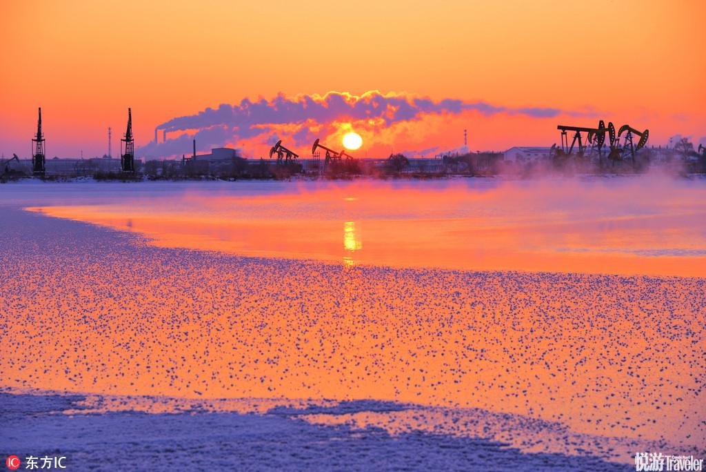黑龙江大庆,每当冬季来临,白雪覆盖了油城大地,在清晨的阳光映照下,白雪、冰面、旭日、抽油机、湖泊、...