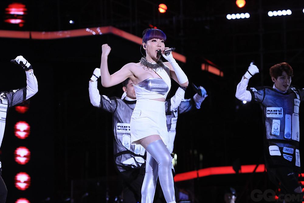 """在这个激战的夜晚,曾经从""""好声音""""走出的优秀学员吴莫愁也再次回到这个舞台,已经成为一名歌手的她,携新歌《大美丽My lips》亮相,而这次的献唱也是她的新专辑首秀。在舞台上她一身简约白色性感服装登台,扎着高高的丸子头,满满都是90后女生的青春气息,古灵精怪的台风与充满正能量的舞蹈表演也彰显出她特立独行的个性。"""