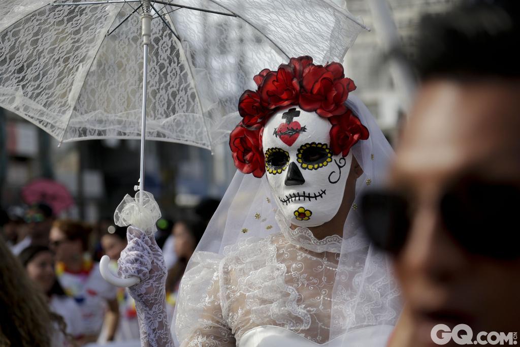 在巴拿马城,一名身穿婚纱和白色面具的男子拿着遮阳伞参加游行,表达了对同性恋合法婚姻的支持。