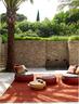 家中的所有陈设都强调自然味道,大量木料和石材的运用,更彰显出建筑的原生态。红色的Dala编织户外家具来自Dedon品牌,圆形木质矮茶几购自Baxter。
