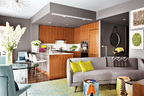 """玻璃窗侵占了墙壁的面积,因此没有足够的空间来悬挂艺术品,设计师决定把地毯作为最主要的""""艺术语言""""。主空间被划分为几个部分,开放式厨房在中间,起居室在右边,左边是餐桌,最左边可以看到通往客房的门,右边画作旁为公寓的入口。灰色沙发由 Santiago Tomás Designs工作室设计,黄色抱枕来自ABC Carpet &Home,瓷凳子出自艺术家Reinaldo Sanguino (RS Ceramics)。"""