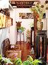 在玄关与客厅的连接处,迟鹏巧妙地用两扇清代硬木雕花窗改造成屏风,与旁边红木高足方花架、清代太师椅形成一道景观。玄关所挂那幅有着裸体背影的摄影作品是他的作品《奔》。