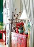 客厅细节,中式红漆木柜与金属烛台的对比饶有趣味。