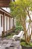 林宪能在原有的建筑物上加建木头回廊及一座流水造景,配上品牌Zanotta的白色户外椅,显现出现代江南园林的精神。