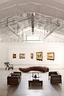 这里果然是一处最好的艺术逃逸地,连用来储 藏艺术品的仓库本身,也像一件不可多得的雕塑。仓库里,中间是经典的柯布西耶LC2沙发椅。17世纪中式的胡桃木茶几台面为竹质。旁边有张洹的作品佛手指。墙上是艺术家郭鸿蔚的油画。