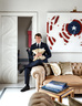 Matteo 坐在起居室的沙发扶手上。他身后的门通往餐厅。背后的画作由意大利艺术家PaoloCeribelli创作。