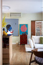 起居空间里结合了当代艺术、现代家具和一些中式元素,完全是东方遇上西方的一场精彩对话!绿玉色的墙上挂着一幅以中国小女孩为主题的油画,是由中国艺术家房辉创作的。白色矮沙发与红色中式边柜,再加上一抹亮黄色,整个起居室流露出轻松又活力十 足的气氛。