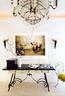 在L.A.Studio购买的上世纪30年代的法式铁制镜面桌,上面摆放着Objetology出售的烛台。墙上挂着在Inés Barrenechea购买的Mikel Uribetxeberría的摄影作品和在David Puente购买的黄铜水晶壁灯。大吊灯是Las Tiendas de San Enrique的,椅子来自Antiq BR。