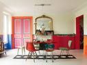 """从世界各地二手市场淘来的宝贝,在红调背景的衬托下可爱而调皮。桌子下的波点地毯来自巴黎Caravane地毯店。原先的人字形木地板被漆成了白色。上世纪60年代的餐桌是从布鲁塞尔的一个集市商人那里买到的,几乎无形的有机玻璃桌腿使它有一种飘浮在半空的感觉,红色桌面为木质。桌旁围绕着购自巴黎St Ouen跳蚤市场的形形色色的椅子。带着透明蓝色塑料椅背的椅子名为""""The Spring Chair"""",是著名设计师Gaetano Pesce的作品。桌子上方小助听筒形状的吊灯来自Tse tse and associes——他们是阿罗拉的巴黎艺术家朋友,在印度生产制造。"""