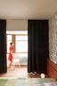 主卧室里,Frekvenssi的黑白壁纸来自Marimekko,与房间的大面积白色形成反差。床头板用来存书,十分实用(由GRAUX & BAEYENSArchitecten设计)。绿色Hay床品为纯色的卧室带来了一抹明亮的心情。