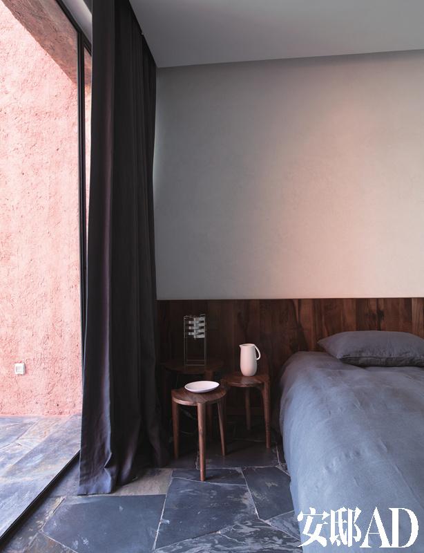 一间卧室中,床头的一组胡桃木小桌同样是来自ko的