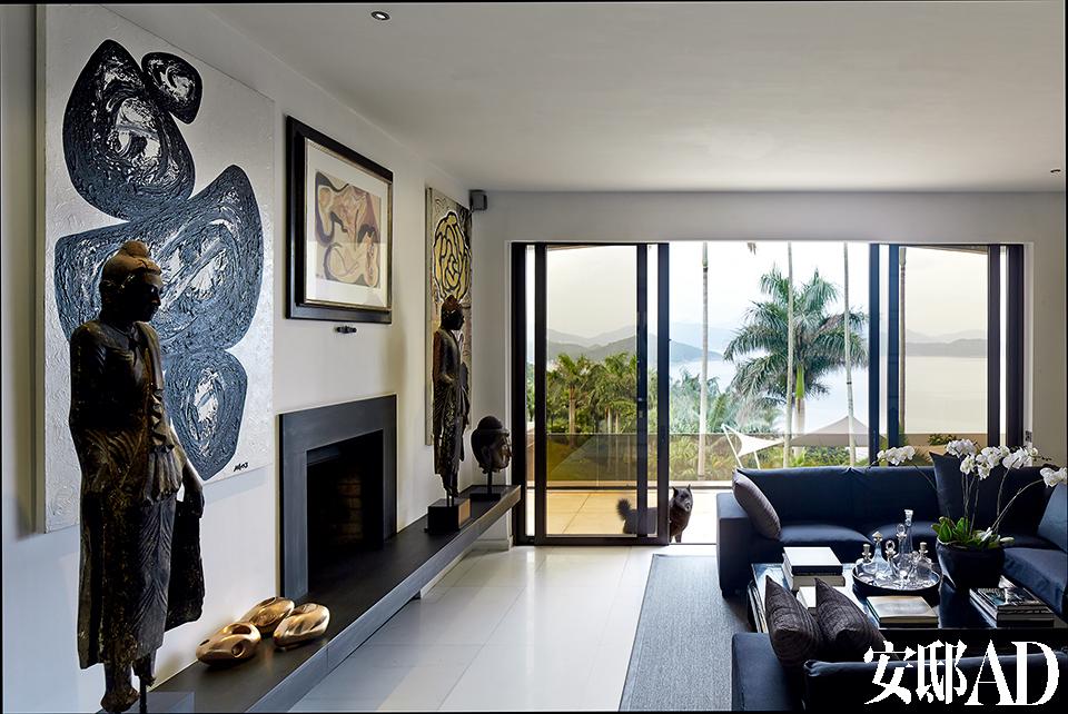 """""""在普吉岛度假酒店的体验,不仅深深地影响了我家的设计,甚至塑造着我在香港的生活方式。""""位于楼上的一处客厅,通过落地窗可以通向一座户外露台。"""