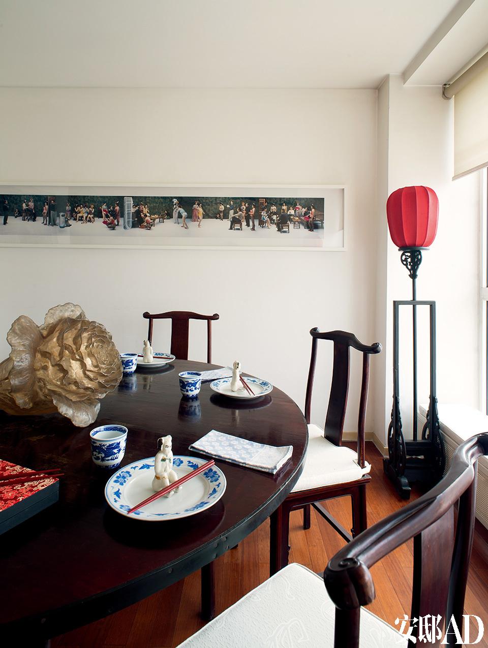 在这里享受一顿家宴,室内是玲珑精致的古色古香,窗外是高速公路的优美弧线,双重景致和着佳肴,令人沉醉。餐厅面积不算大,刚好放下这张圆形大餐桌,每当布置家宴,Sylvia从各处收来的古董小摆件就会派上用场。墙上的摄影作品由当代摄影艺术家王庆松创作于2000年,每一个场景里都有艺术家本人出镜。红灯笼落地灯购自朝外古董市场。