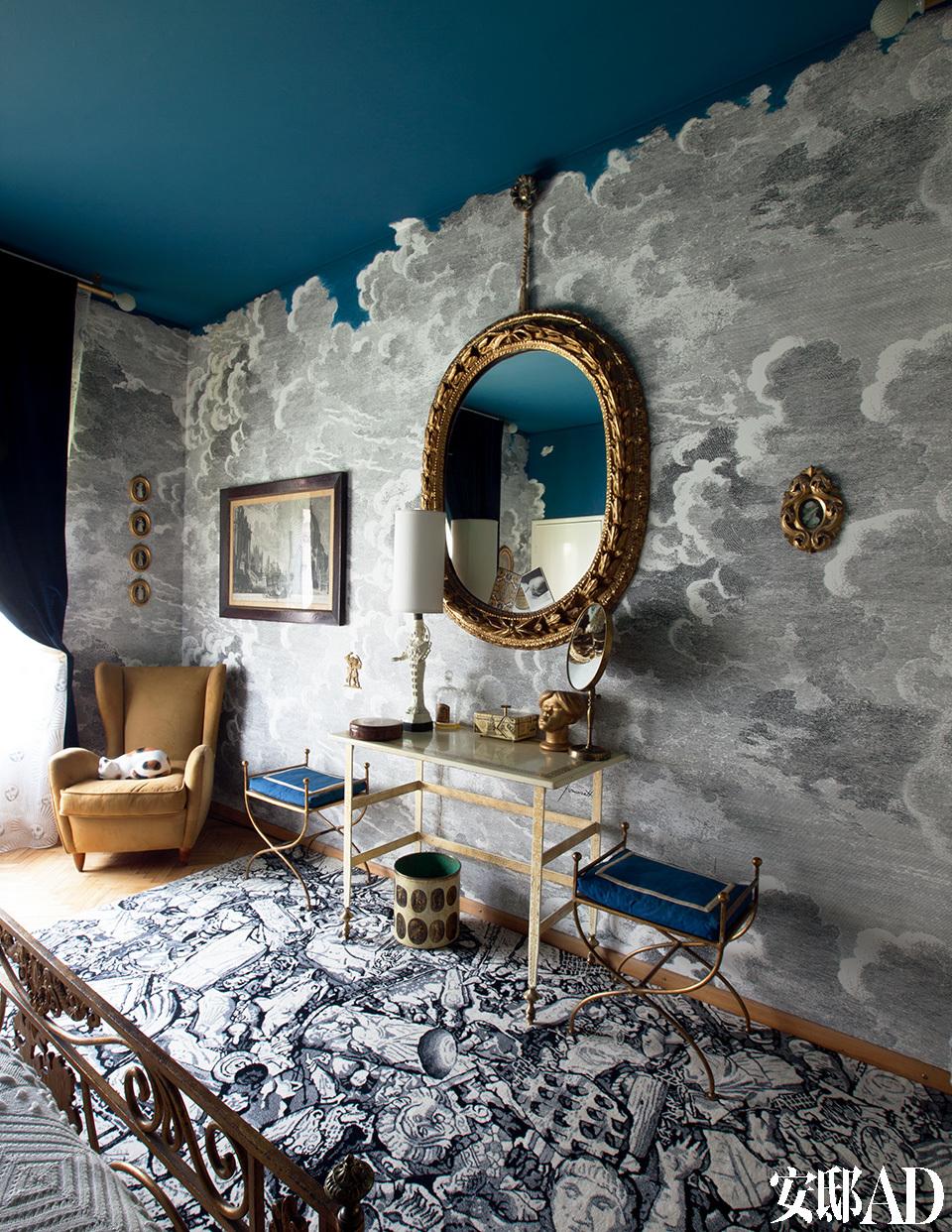 """卧室墙面上的""""蓝天白云"""",令人陶醉在一个风起云涌的童话故事中。Piero Fornasetti位于家二层的卧室。墙纸""""Nuvolette""""是Fornasetti先生的原创作品,至今仍被Cole&Son公司制作生产。这个房间已经个性化地被换掉顶部,墙面全部被漆成了蓝色,来获得梦一般的效果。"""