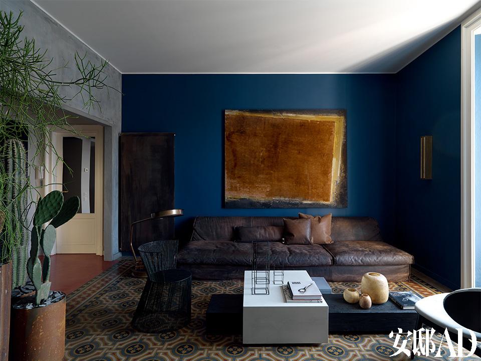 老旧的地砖,以质朴、静默的色调,主导着客厅。宽大的棕色皮质沙发占据了几乎一整侧的位置,沙发上方深蓝色墙面上悬挂着的艺术品,与一旁硕大的金属落地阅读灯,都使用了相近颜色。暖气被藏在一块巨大的金属板后面,与室内陈设所使用的基调和谐地相处。