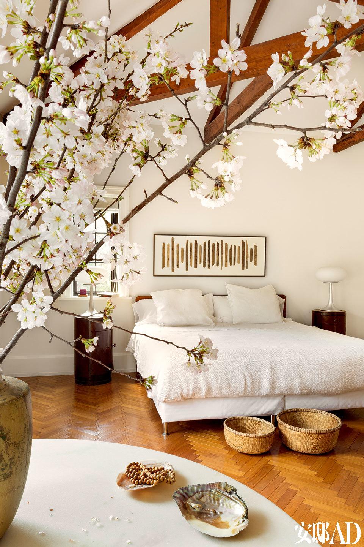"""床头的艺术品是Claire的母亲送给他们的新婚礼物,""""妈妈总是用日常发现的废弃物来创作,她让我懂得,要从简单的事物中去寻找美、发现美。""""主卧也是白色为基调,角落的一张大桌子专门用来放大枝的插花。"""