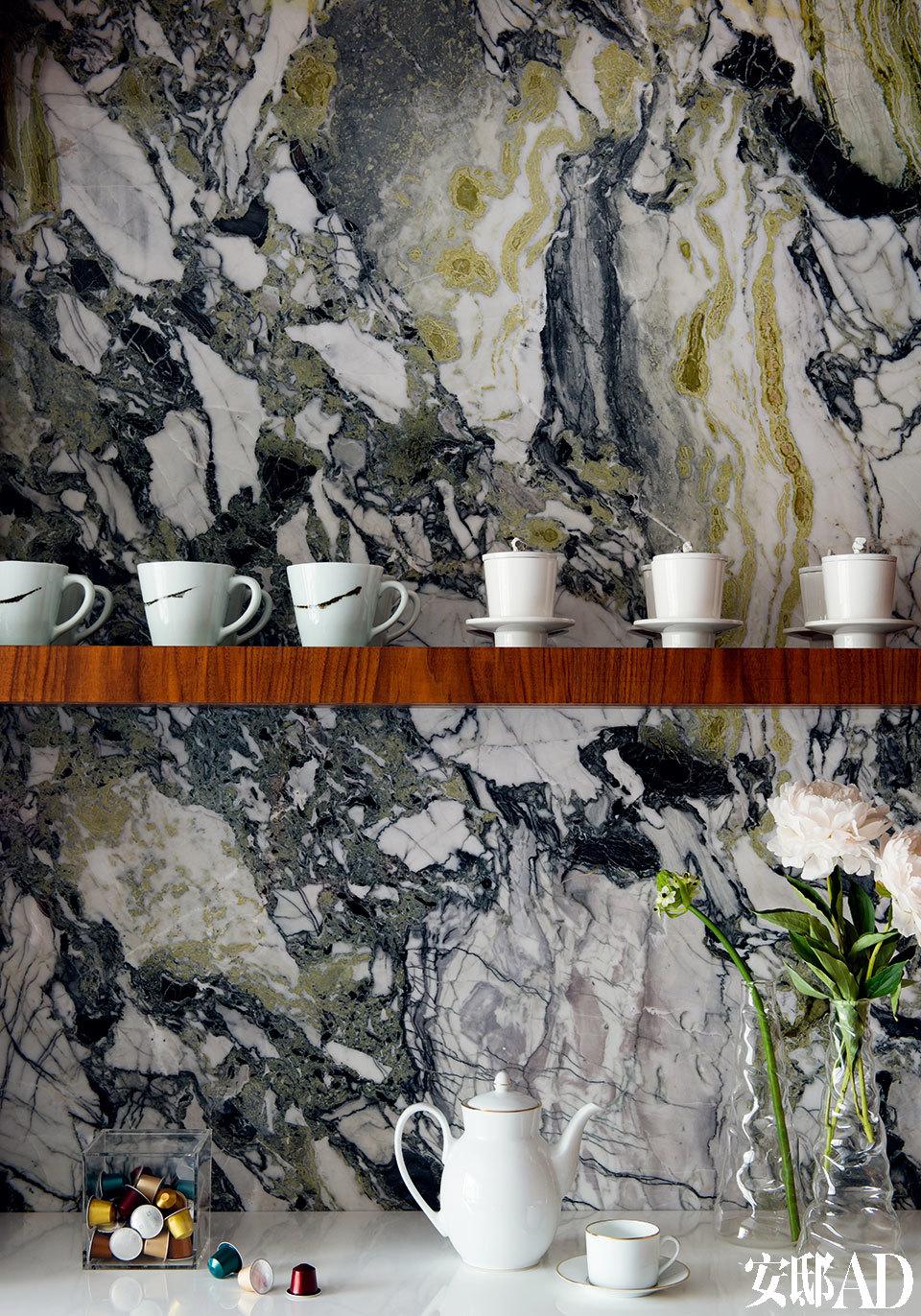 一块纹理、色泽都非常精美的云龙白玉大理石,成了家中三种主色调的灵感之源。早餐厅中装饰着一面云龙白玉大理石墙壁,架上的瓷器和台面上的茶壶均由Gary Wang设计,来自Spin。