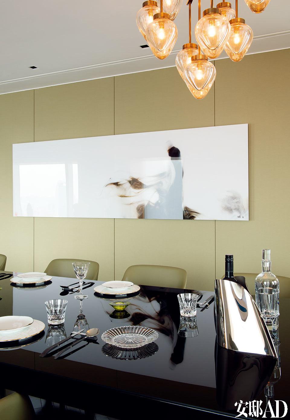 餐桌旁墙面上的艺术品由Lu Jun创作,来自Elisabeth de Brante,吊灯同样来自Holly Hunt。