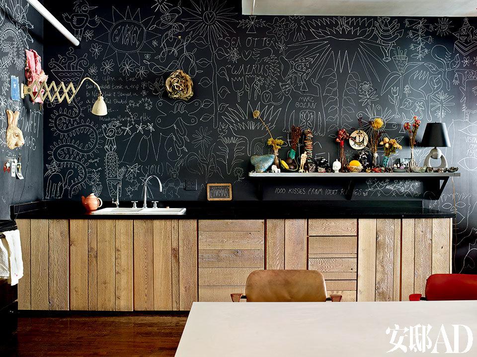 使用环保木材装饰的厨房活泼有趣,一整面墙的手绘黑板画,褪去了色彩,褪不掉线条的趣味张力。厨房的壁板上有各种图案的艺术画、从二手市场淘来的兔子面具、伸缩式小台灯和小茶壶。壁炉架上,有各式各样的陶器、干花和小装饰品。