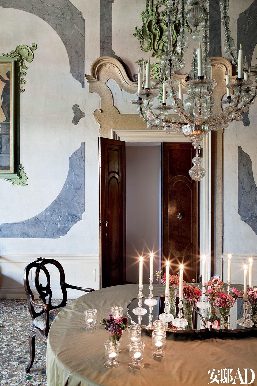 在这栋住宅正式用餐的房间里,到处都装点着典型的威尼斯风格内饰,比如18世纪的枝形水晶吊灯、有趣的墙面,意大利Murano的杯具、餐具,以及18世纪的威尼斯古董椅。