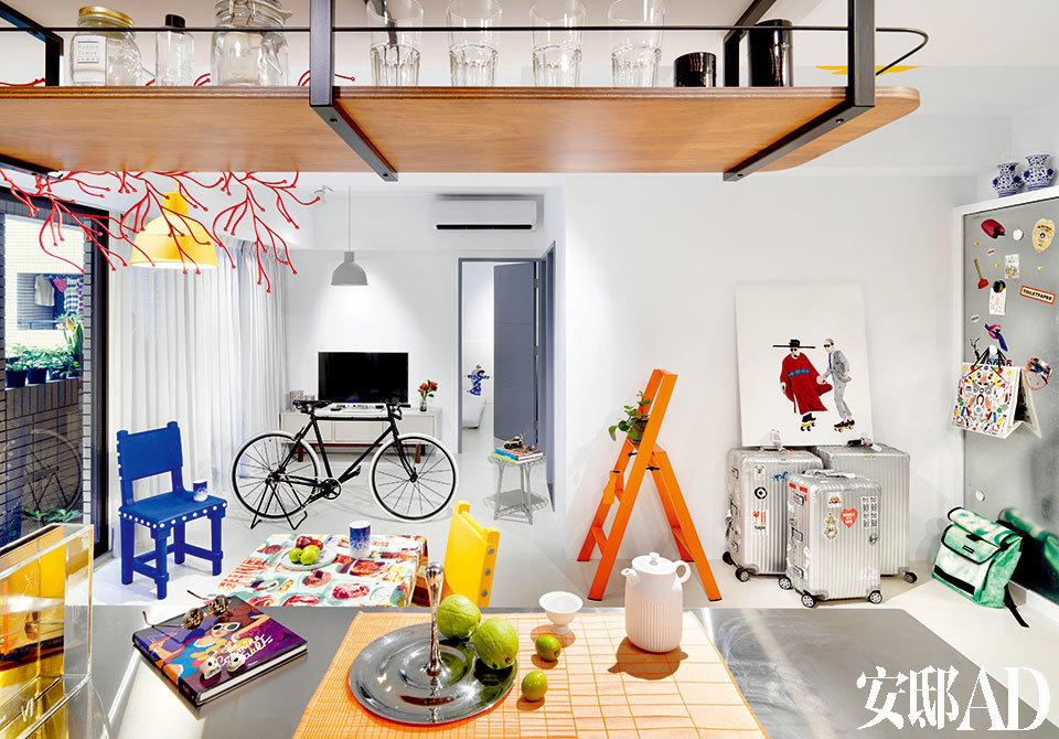 """把厨房的隔断打通,最大化地扩展客厅视野。而色彩跳跃的设计单品则点亮了整个空间,显示出当下年轻人对生活品质的追求与判断!客厅与厨房开放相连,岛台上,银色水果盘来自Royal VKB,是荷兰设计大师Gijs Bakker 2005年的设计,下面的茶席布来自HAY,白色瓷器茶壶与茶杯来自Lyngby Porcelæn ,是Pili自己2012年的设计作品。客厅中间,黄色与蓝色座椅来自Moooi,名叫""""Gothic Chair"""",是Studio Job在2011年推出的作品。黄色与灰色的吊灯来自Mutto,银色如竹编织状的小凳其实是一张小桌,是日本设计师Nendo 2012年的作品,来自Han Gallery。旅行箱上的和远处客卧里的油画均来自年轻艺术家""""只是"""",他也是Pili学设计时的同班同学。"""