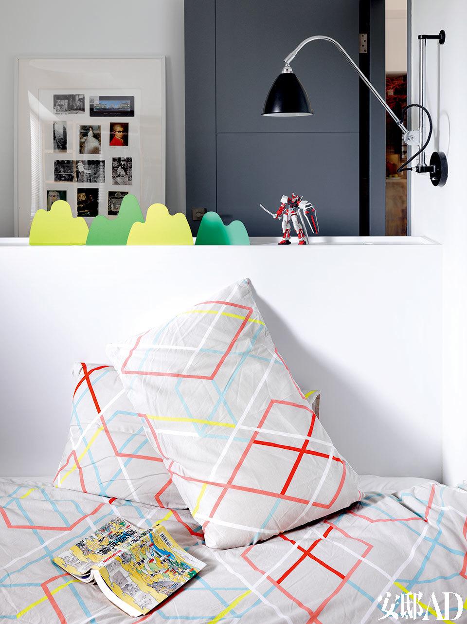 """从另一个角度看卧室,黑色床头壁灯来自Gubi,是Robert Dudley Best在1930年推出的设计作品。远处门边放置的板框内就贴着Pili在维也纳实习期间寄回家的经过了他""""加工""""的明信片们。"""