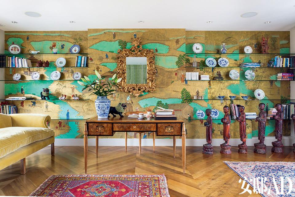 """描绘中国清代时期生活场景的贴金箔手绘壁纸,""""看其中的故事,想象当时人们的生活,看上一整天也不会腻。""""三层客厅的另一面。Art Deco风格的书桌来自法国,制作于1935年。桌上的青花瓷瓶是de Gournay根据Claud的一只中国明代花瓶而在景德镇仿制的,并只仿制了这一只。而花瓶旁边的狮子是19世纪缅甸佛寺里的艺术品。墙上的金色镜子是Claud在法国买到的18世纪洛可可风格的意大利镜子,他又在英国重新为它贴了金箔。壁纸是de Gournay中式系列的Coutts。"""