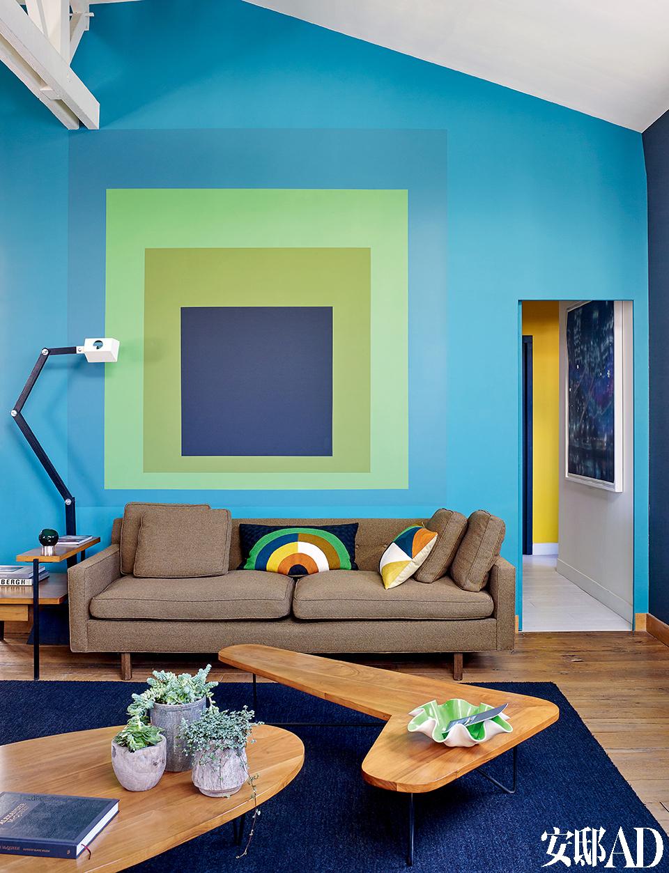 """沙发上方""""的 抽象画 ,""""其实是彩色涂料换了种特别的涂法,设计师说:"""" 家里的艺术品不应是永久陈列的,一旦你厌倦了, 不妨来点儿变化!""""客厅里的沙发是美国家具设计师Edward Wormley于20世纪60年代创作的经典作品,面料仍是当时的原作。沙发上摆放着Lindell & Co出品的靠垫。一侧的关节造型灯具Architect是Florence Lopez的新作,灵感来自一盏20世纪50年代的工作灯。"""