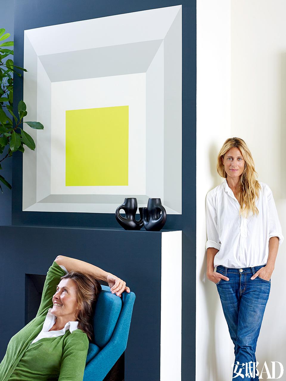 设计师Florence Lopez躺在椅子上,屋主Natacha Sénéchal则靠在壁炉旁。壁炉上方是Florence向美国抽象艺术家Josef Albers致敬的画作。 设计师: Florence Lopez(左),法国古董商兼室内设计师,出生于阿根廷,现居法国,时常游走于其位于巴黎的公寓兼古董买手店和位于波尔图的酒庄。她在室内设计领域不曾走过寻常之路,更因她对空间色彩的巧妙运用令人印象深刻。目前,她还在为一间纽约的阁楼、一栋香港海景别墅和柏林一座大型消防站进行室内设计工作。与此同时,她还与她的丈夫、建筑师Patrick Hernandez一起设计家居小物。www.florencelopez.com