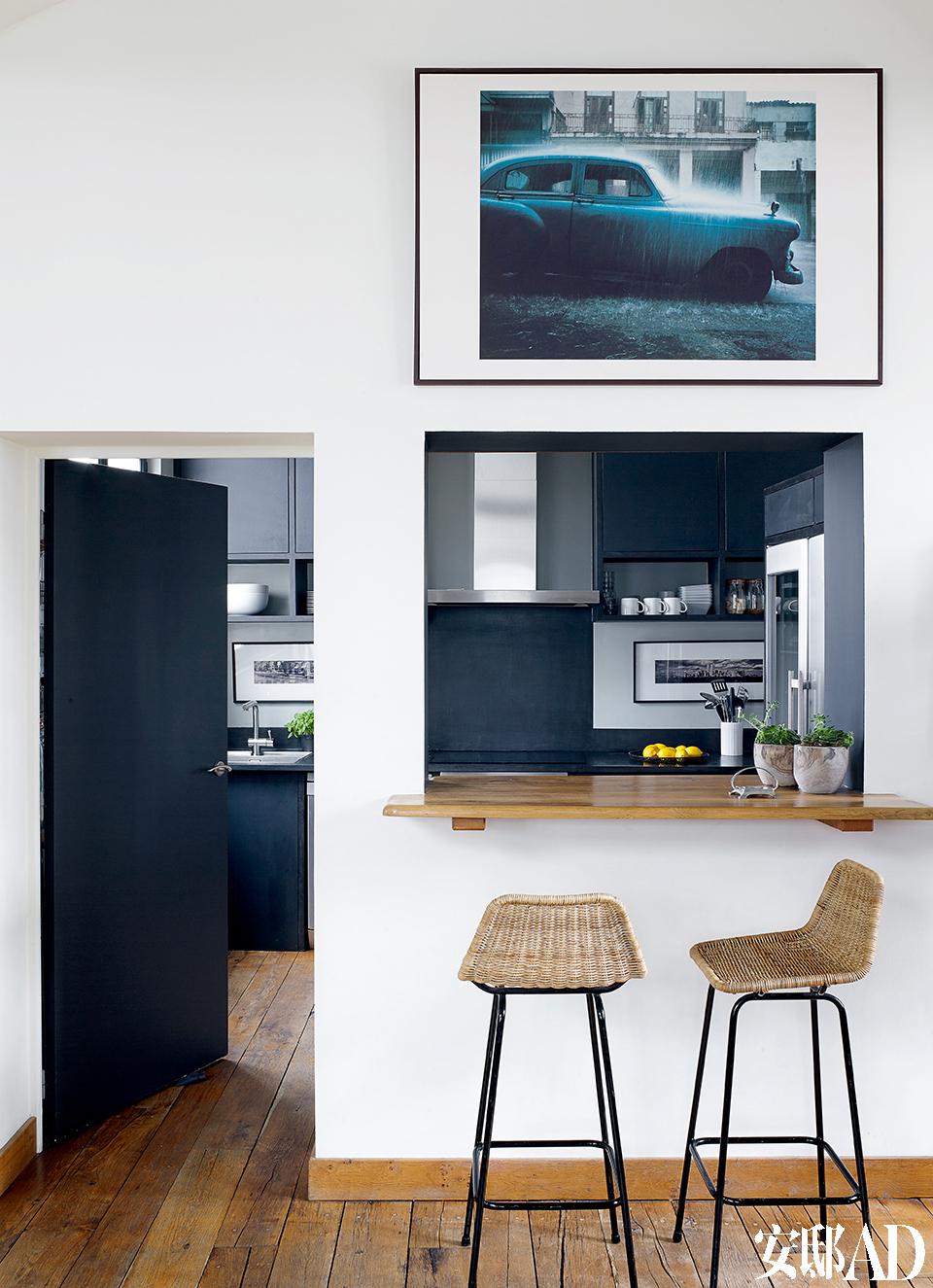Florence Lopez用吧台的设计 打通了客厅与厨房。藤编高脚凳是Mimbre的古董家具。吧台上方的摄影作品是法国著名摄影师Thierry Le Gouès在哈瓦那拍摄的一系列美国汽车中的一幅。