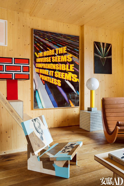 客厅近处的椅子是Rabbit Chair (Low Rider Series),这是Richard Woods 2014年的作品。Vintage风格的真皮软垫摇椅Relaxer是 Verner Panton为 Rosenthal Studio设计的模型。左边小柜子上的红砖台灯(Red Brick Lamp)也是Richard 2014年的作品。墙上的艺术品,左边那幅是Mark Titchner 1995年的作品《无题》,右边的是Lillian Vaule 2008年的作品《无题》。