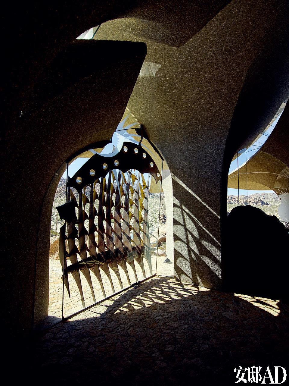 """小屋恢弘壮观,充满神秘感和艺术感,图为骨骼式样的仿吊闸门。""""就这样一头跳下'了悬崖',边坠落,边想着怎么给自己装'上翅膀' """"。主人如此描述这栋房子的艰难的建造历程。"""