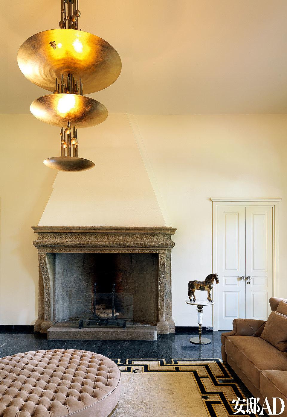 17世纪的古老壁炉迎来了现代风格的艺术吊灯,在Cavalli先生的客厅中幻化为新老相融的诗句。客厅的一侧,源自17世纪的壁炉前摆着Reginald圆坐垫,非常惹眼的Zeus金属吊灯由Alessandro La Spada设计,以上产品均来自Visionnaire。