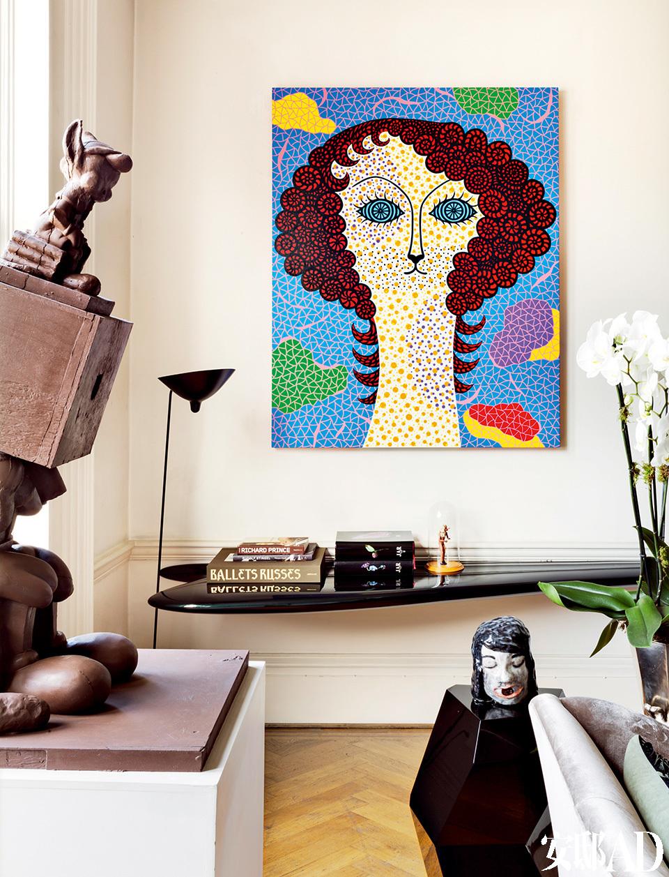 在这个家里,处处是设计得有如一件艺术品,却又兼具功能性的生活物件,艺术和设计已不那么泾渭分明。客厅的一角,墙上的画作来自日本艺术家草间弥生,画作下方的黑色搁架由Zaha Hadid设计,墙角的黑色落地灯来自Serge Mouille,白色立柱上摆着Paul McCarthy设计的树脂雕塑品。沙发旁的黑色几何形小茶几由Mattia Bonetti设计,茶几上的陶瓷头像是Klara Kristalova的作品。