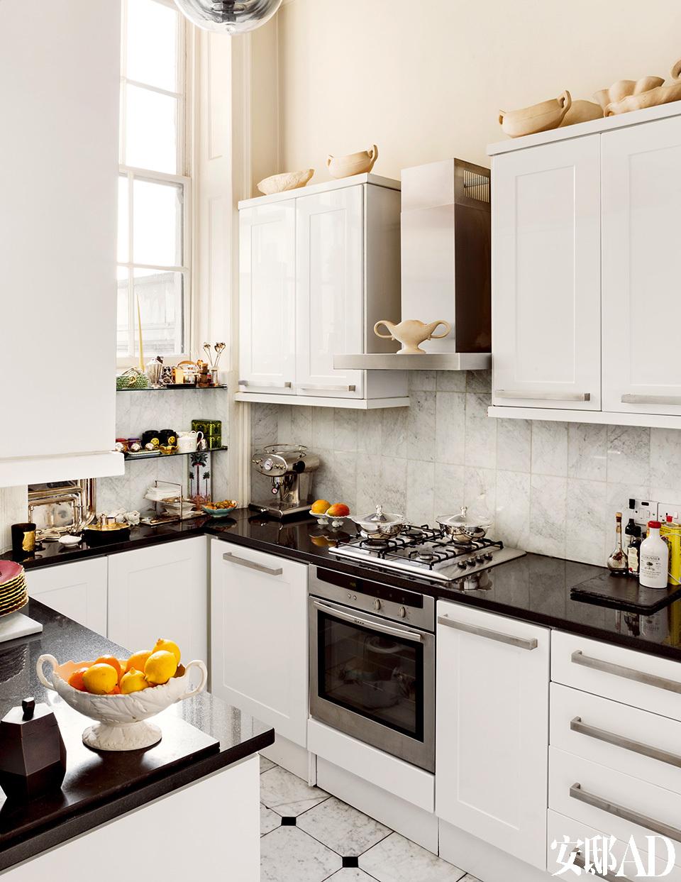 厨房天花板上悬挂着Tom Dixon设计的吊灯,橱柜上的瓶瓶罐罐均来自Constance Spruy。