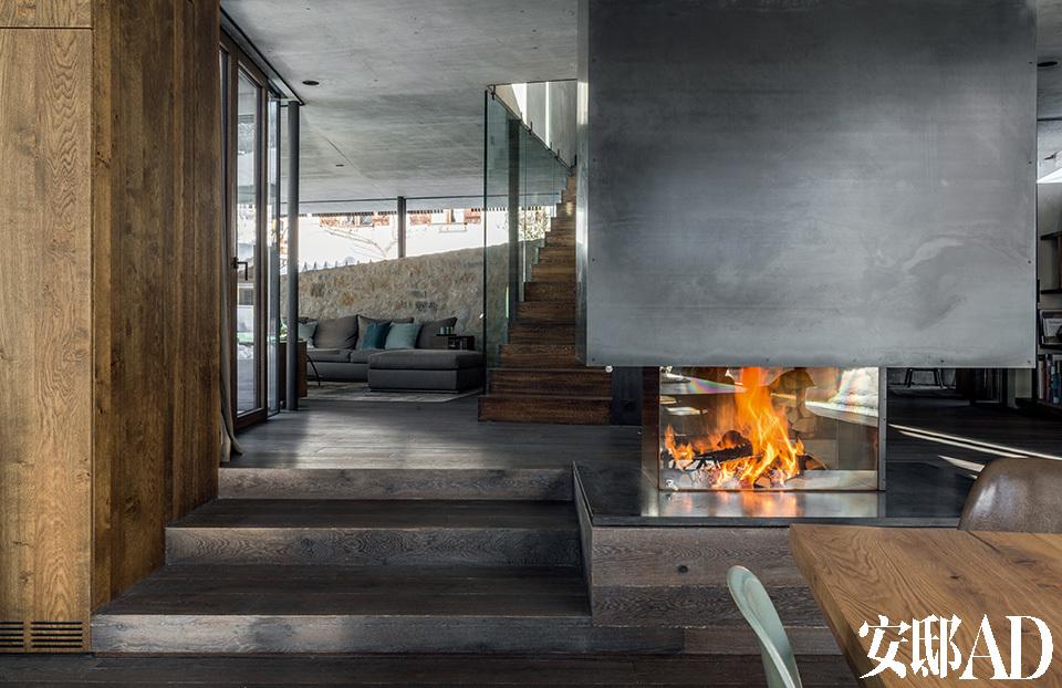 极具特色的开放式火炉在前方的餐厅和后方的起居室中间,是Monika Gogl工作室Gogl Architekten设计的,并由当地的炉子装配工完成。橡木制成的地板和家具、以及钢筋、玻璃等用料,是典型的阿尔卑斯式的材质,这与用水泥制成的地面层天花板形成强烈的反差。远处的楼梯通往楼上的主卧和浴室。