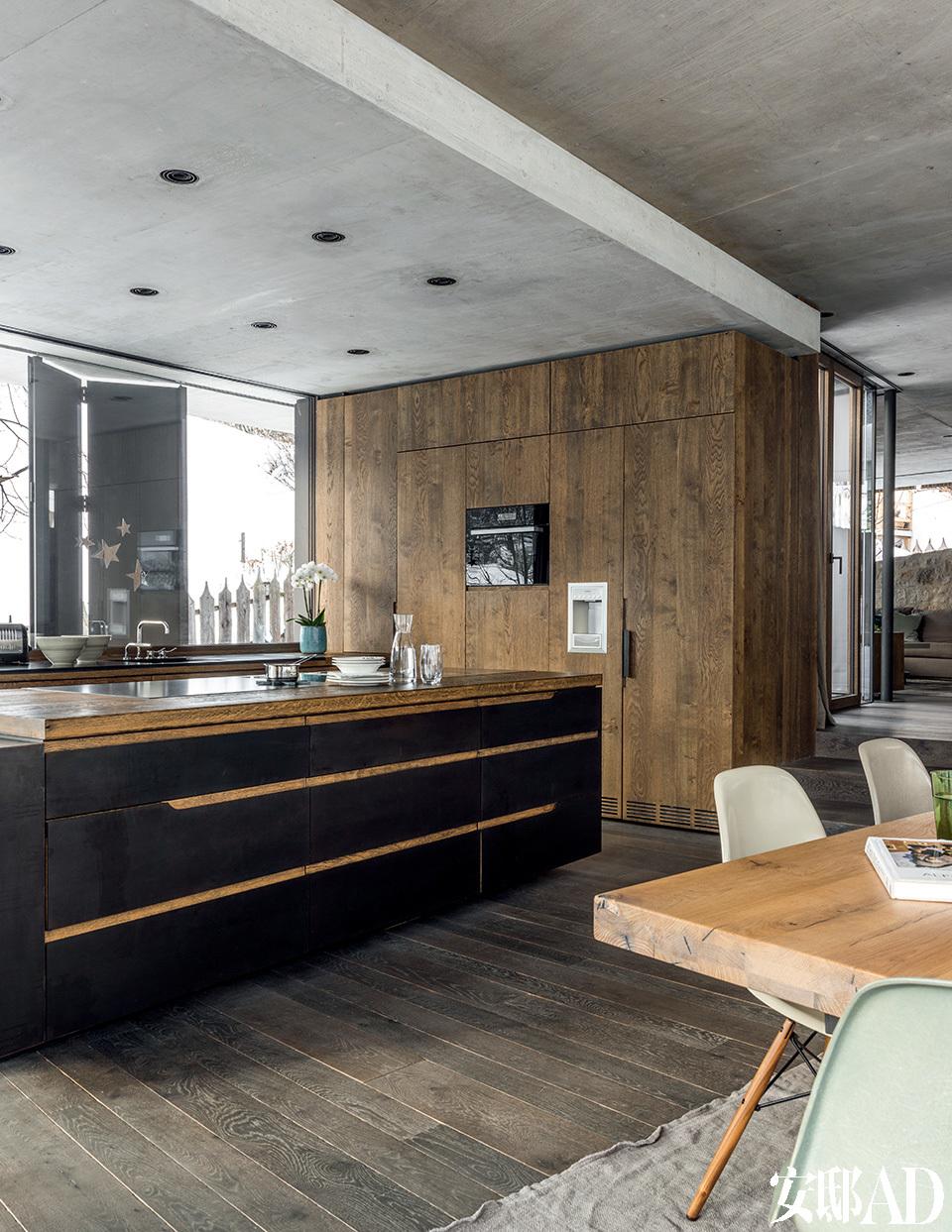 建筑师别具匠心地为新屋的厨房选用了黑钢和橡木材质。