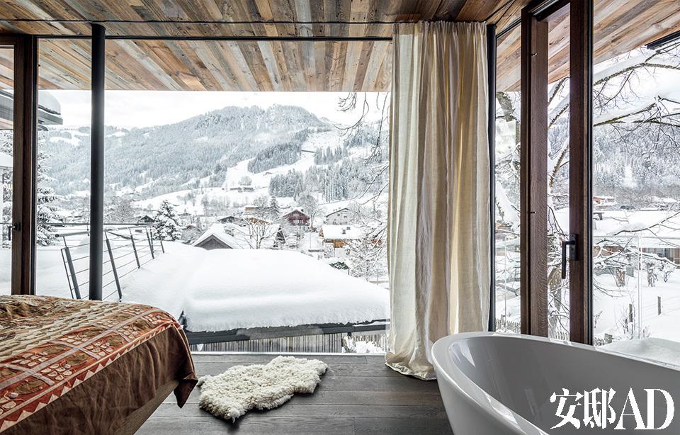 白雪皑皑中, 躺在拥有无敌雪景的浴缸里,真是一种浪漫又奢侈的享受!整个主卧的地板和天花板都是由橡木制成的。在极佳位置的大浴缸里泡个澡,能享受到阿尔卑斯山的壮观美景,还能顺便看到Streif雪坡。大床是由当地木匠Tischlerei Hofer制作而成。