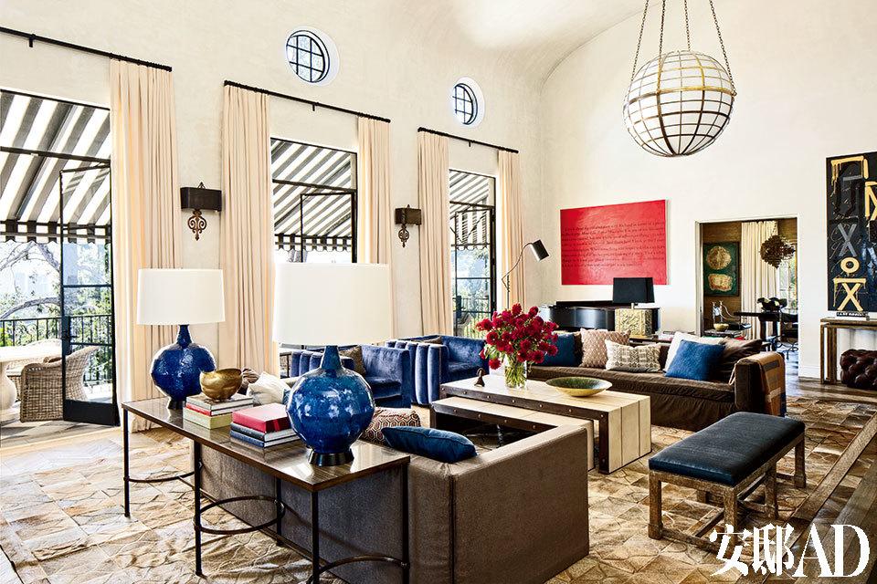 为了让宽大的客厅更显私密亲和,设计师布置了超尺寸的门窗、家具、吊灯和地毯,加州的阳光更为一切镀上金色光晕。主客厅中布满了定制家具,落地门窗由木结构的法式对开门换成了高达3.4米的黑色金属框玻璃门,黄铜吊灯由Bullard设计,宽大的沙发采用了Schumacher棕色马海毛丝绒面料,窗帘也来自这个品牌,沙发上的毛毯来自Hermès,1940年代风格的单人俱乐部椅选用了蓝色丝绒外包,一大块带有阿拉伯式花纹的Mansour Modern牛皮地毯让这个大空间显得柔和了许多。鸡尾酒桌由Jean de Merry设计,墙上红底带字的油画是Claire Fontaine的作品。