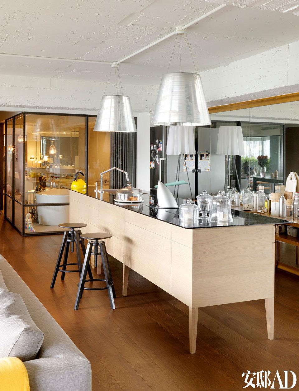 """""""客厅大,室内空间看起来就大。我特别将家的1/2留给客厅和餐厅,让到访的朋友能更随意交流。""""大型中岛台为厨房,为了美观,包益民舍弃抽油烟机,以电炉为主。镶了金框的镜墙,内有隐藏柜子,空间看来更加宽阔,天花吊着Philippe Starck设计的""""Miss K""""吊灯。"""