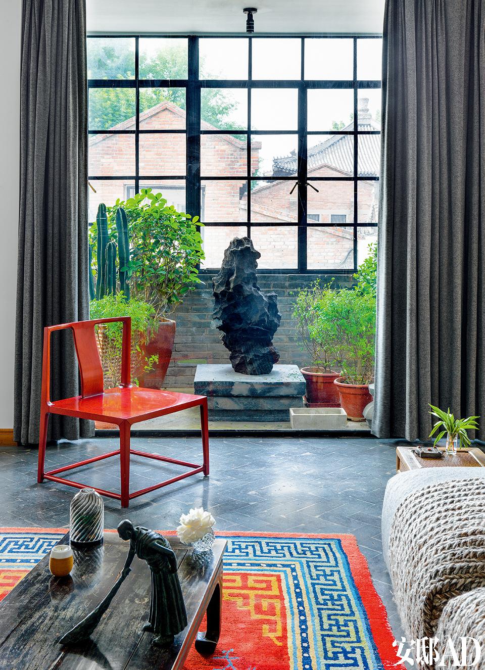 从窗口往外眺望,一边是车水马龙的市井胡同,一边是600年的古寺瓦楞。红色中式椅子来自「上 下」。阳台上海绵材质的太湖石 雕塑是孙文涛的作品。