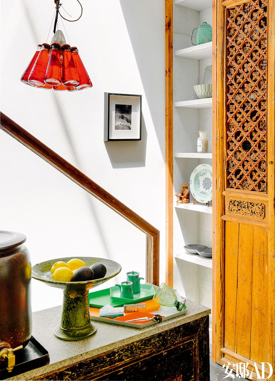 厨房上方是通透的玻璃窗,阳光倾泻,做饭的时光由此变得格外美好。厨房里可乐瓶式吊灯来自他很喜爱的灯具品牌Ingo Maurer。与墙体相连的储物柜里放置着他收藏的老瓷器摆件。