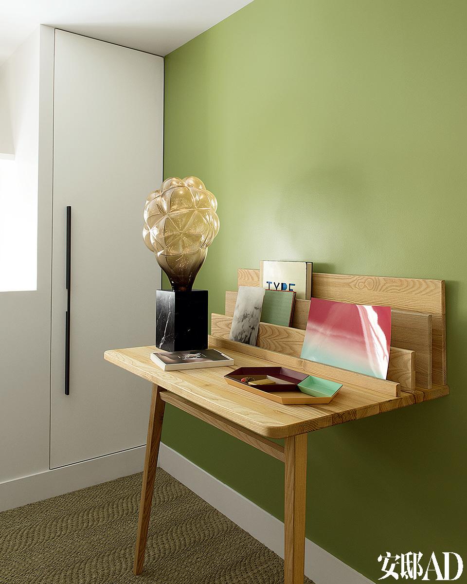 """卧室床对面有一张Margaux Keller的""""Scriban""""书桌(来自La Redoute的Sam Baron系列)和一盏Mathieu Lehanneur的""""Smoke"""" 台灯(来自Carpenters Workshop Gallery)。桌上的托盘来自Hay chez Silvera。"""