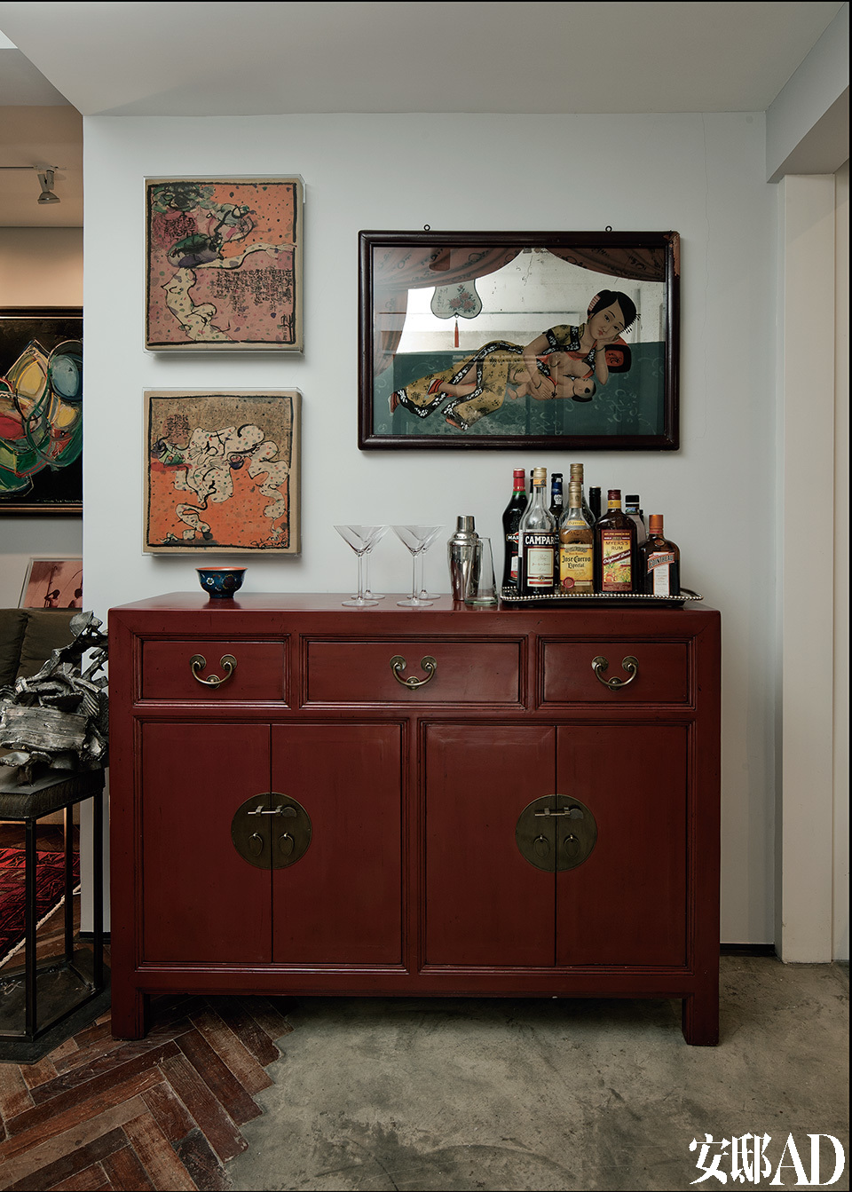 客厅通向餐厅的过道,在这里传统中式家具和中西艺术品搭配得恰到好处,红色漆柜起着餐柜的作用。