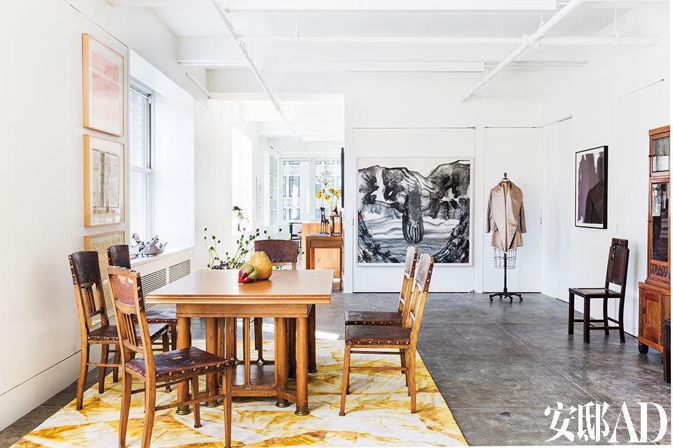 """客厅以及远处的厨房和餐厅。近处的方桌和5把椅子是20世纪初期的奥地利古典家具,它们位于一块韩枫为香港Tai Ping(太平地毯)品牌设计的地毯""""Yan""""上。椅背靠着的墙面上并列挂着的3幅作品由画家路青创作,正对面墙上是谷文达的山水画《超然》,它旁边挂着 的一件外套由韩枫设计,再右侧的画作则来自王冬龄。"""