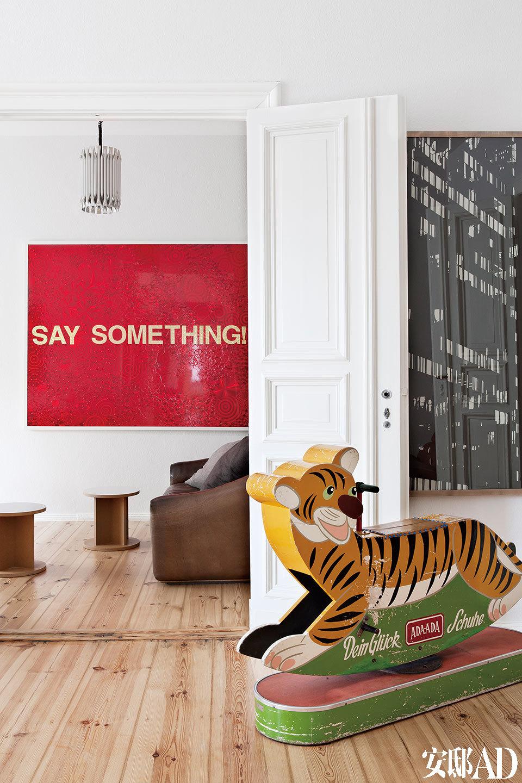 """""""如今,生活在图像海洋中的我们,常常接受着各种视觉刺激,在无意中消费着图片。""""墙上醒目的红底色作品《Say Something》来自GoranTomcic,近处的黑白摄影作品是 Stefan Thiel拍摄的一栋建筑物,摇摇椅则是从一家商店里淘来的旧物。"""