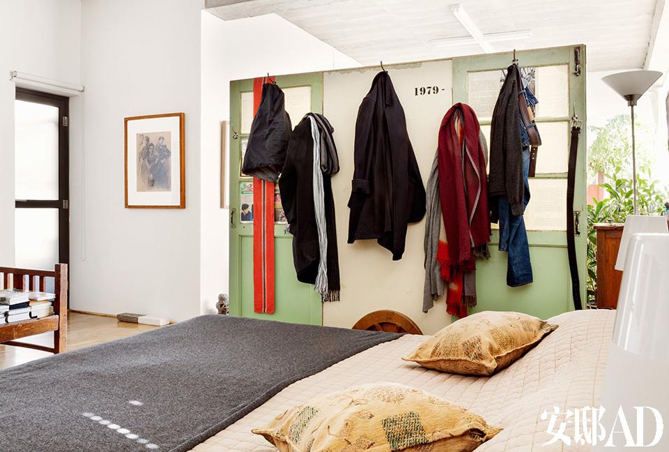 绿色旧木门上悬挂着和服和长衫,黄锐出门长衫居多,在家则和服居多,旧木门改造成的屏风既起到了隔断的作用,又具有实用性。