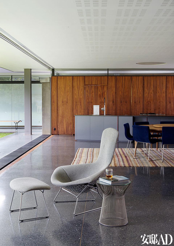 远处的餐椅是Pascal Mourgue的Ligne Roset Sala Chairs。近处的Bird Chair和搁脚凳是Harry Bertoia为Knoll设计的作品,还有Warren Platner的边桌也来自Knoll。经抛光的水磨石地板中的接合处嵌入了黄铜带,更增精致感。