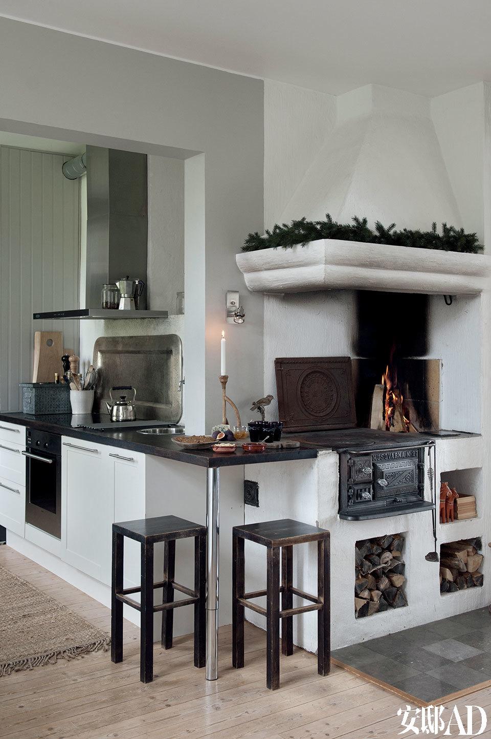 重新改建的老旧木制火炉成了厨房的核心,厨房里的细木家具来自Marbodal,橱柜上的操作面被漆成了黑色是为了配合Ylva父亲Ove曾制作的托盘。