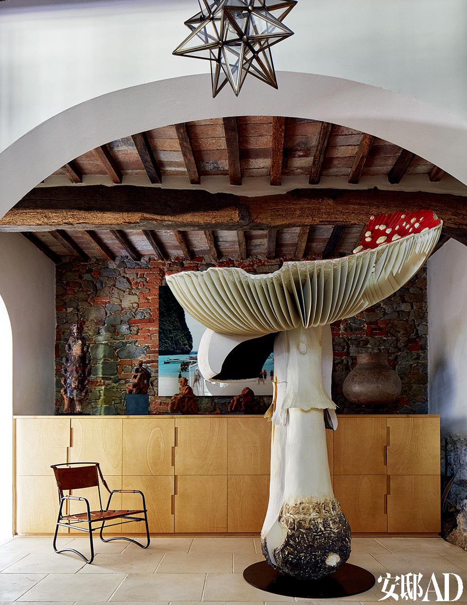 铁制皮革面料座椅由Jacques Adnet设计。2.6米高的Giant Triple Mushroom 大蘑菇艺术摆件来自Carsten Höller。后方的摄影作品来自意大利摄影师Francesco Jodice。